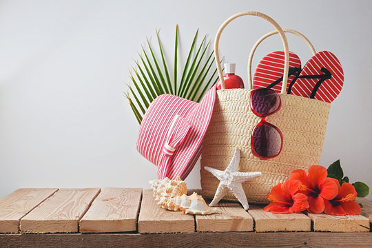 beach bag with beach apparel, flowers, and shells