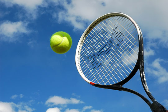 tennis ball and racket against a blue sky background